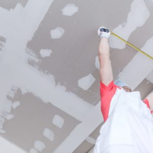Drywall Construction Measurement by Caucasian Worker.
